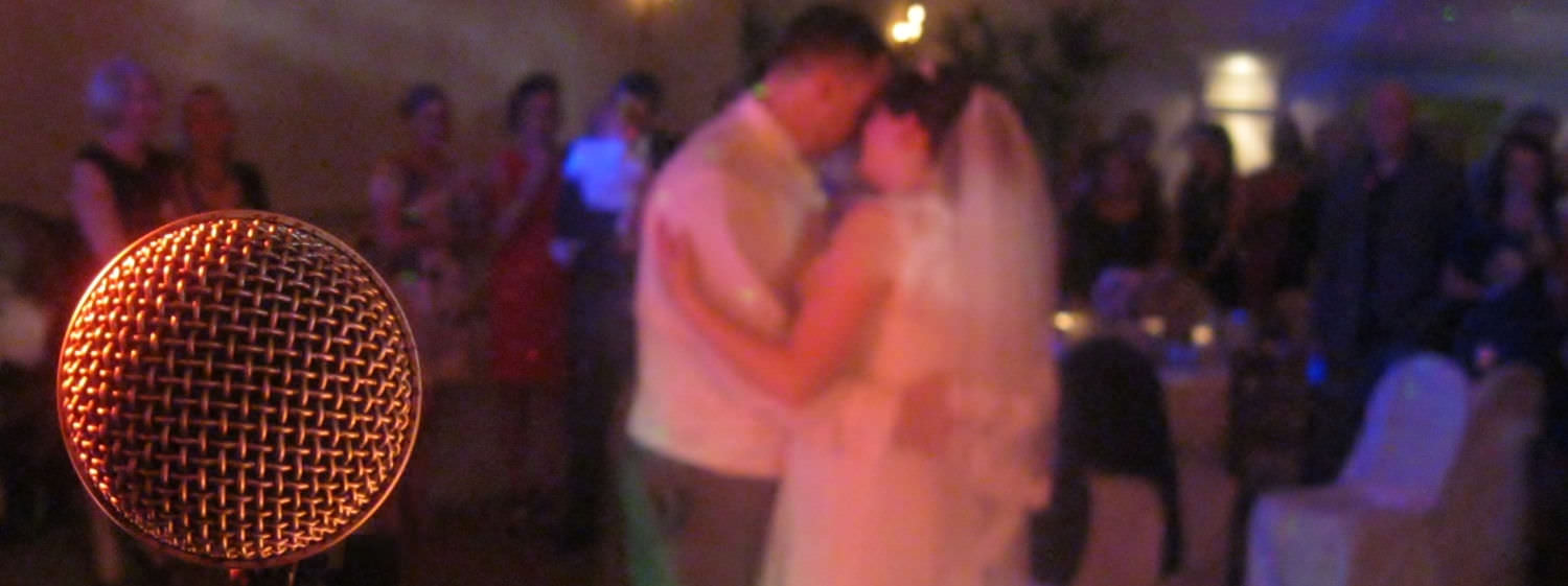 A microphone in the left foreground reveals bride and groom embraced in centre of dance floor with friends gathered behind.